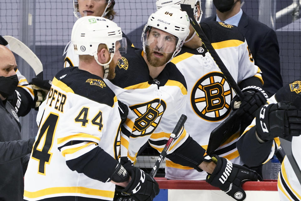 FILE - Boston Bruins' Jarred Tinordi, right, is helped from the ice by Steve Kampfer (44) after taking a hit from Pittsburgh Penguins' Brandon Tanev during the second period of an NHL hockey game in Pittsburgh, in this Tuesday, March 16, 2021, file photo. Pittsburgh captain Sidney Crosby and Washington winger Tom Wilson separately questioned the NHL on a lack of clarity between clean and dirty hits. Crosby did it after teammate Brandon Tanev was given a major penalty for a hit on Boston's Jarred Tinordi that might not have been illegal at all, and Wilson after he served a seven-game suspension for boarding that wasn't called on the ice. (AP Photo/Keith Srakocic, File)