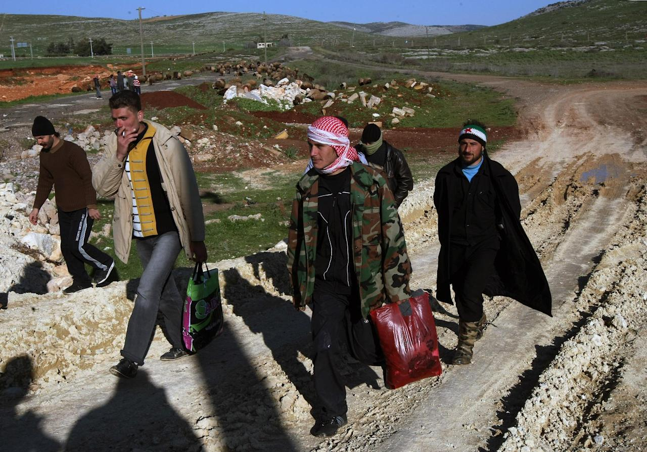 A group of Syrians, fleeing violence in their country, walk toward a refugee camp after they have cleared barbed wires to enter Turkey near Reyhanli, Turkey, Saturday, March 17, 2012. News reports say about 1,000 Syrian refugees arrived on Wednesday. (AP Photo/Burhan Ozbilici)