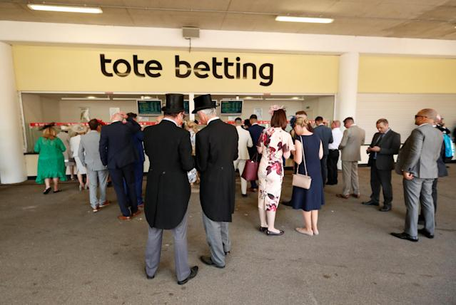 Horse Racing - Royal Ascot - Ascot Racecourse, Ascot, Britain - June 21, 2018 Racegoers place bets at a stall Action Images via Reuters/Andrew Boyers