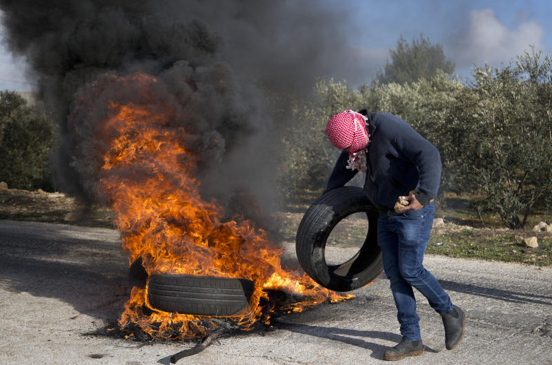 A masked Palestinian protester sets tires on fire during clashes with Israel forces as they protest Middle East peace plan announced Tuesday by US President Donald Trump, which strongly favors Israel, at Beit El checkpoint, near the West Bank city of Ramallah, Wednesday, Jan 29, 2020 (AP Photo/Majdi Mohammed)