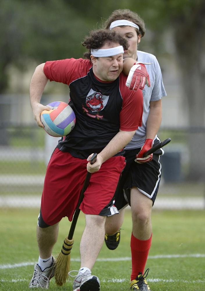 Silicon Valley Skrewts' Will Hack, left, gets hit in the face while trying to keep the quaffle away from Rollins College's Stephen Nettles during a scrimmage at the Quidditch World Cup in Kissimmee, Fla., Friday, April 12, 2013. Quidditch is a game born within the pages of Harry Potter novels, but in recent years it's become a real-life sport. The game is a co-ed, full contact sport that combines elements of rugby, dodgeball and Olympic handball. (AP Photo/Phelan M. Ebenhack)