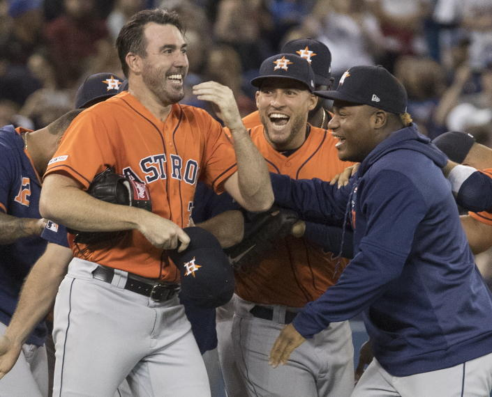 Houston Astros starting pitcher Justin Verlander, left, is mobbed by teammates after pitching a no-hitter against the Toronto Blue Jays in a baseball game in Toronto, Sunday, Sept. 1, 2019. (Fred Thornhill/The Canadian Press via AP)
