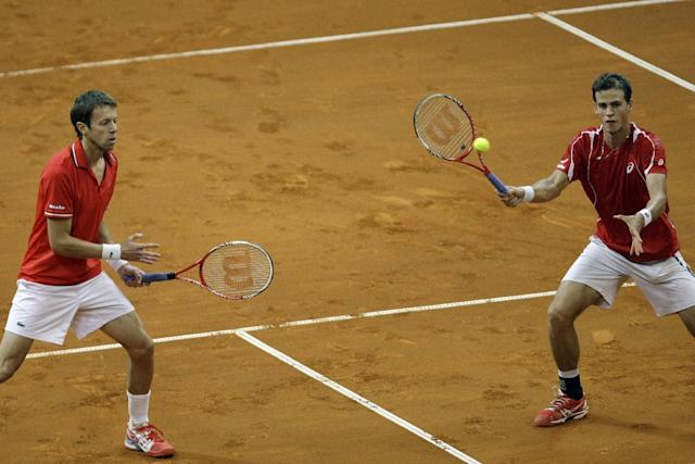 Canada's Vasek Pospisil, right, returns a ball as partner Daniel Nestor follows the action during their Davis Cup semifinal tennis doubles match against Serbia's Nenad Zimonjic and Ilija Bozoljac in Belgrade, Serbia, Saturday, Sept. 14, 2013. (AP Photo/Marko Drobnjakovic)