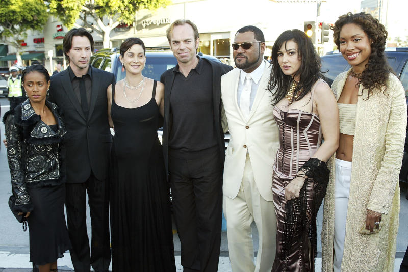 "LOS ANGELES - MAY 7: Cast members (L to R) Jada Pinkett Smith, Keanu Reeves, Carrie-Anne Moss, Hugo Weaving, Laurence Fishburne, Monica Bellucci and Gina Torres arrive at the premiere of ""The Matrix Reloaded"" at the Village Theater on May 7, 2003 in Los Angeles, California. (Photo by Kevin Winter/Getty Images)"
