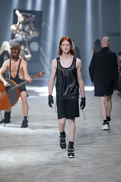 A model wears a creation by fashion designer Rick Owens as part of his men's fashion Spring-Summer 2014 collection, presented Thursday, June 27, 2013 in Paris, as Estonian metal/punk band Winny Puhh perform live, rear left. (AP Photo/Francois Mori)