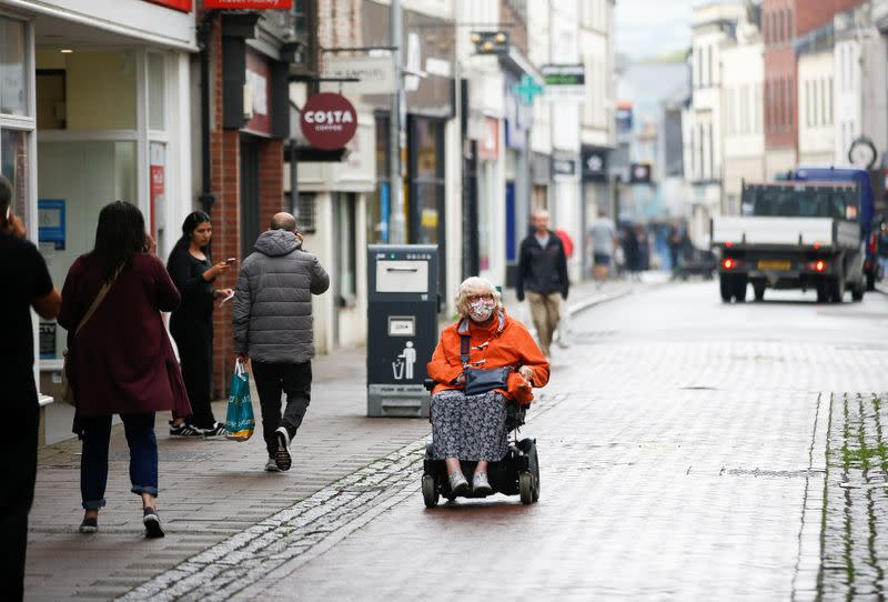 An elderly woman wearing a protective face mask moves on the High Street in Barnstaple