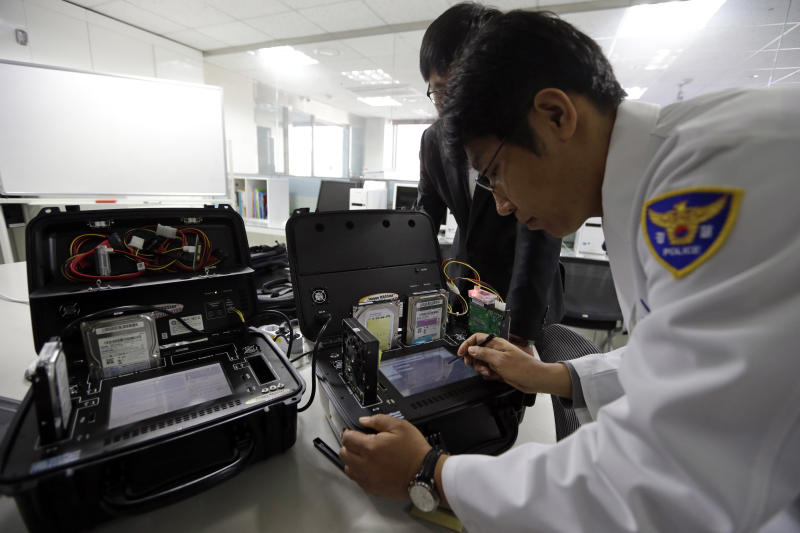 South Korean computer researchers check the shutdown hardwares of Korean Broadcasting System (KBS) at Evidence Acquisition Lab of Cyber Terror Response Center at National Police Agency in Seoul, South Korea, Thursday, March 21, 2013. A Chinese Internet address was the source of a cyberattack on one company hit in a massive network shutdown that affected 32,000 computers at six banks and media companies in South Korea, initial findings indicated Thursday. (AP Photo/Lee Jin-man)