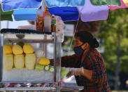 A masked fruit vendor prepares her streetside cart while waiting for customers near downtown Los Angeles on Wednesday, Aug. 5, 2020. California lawmakers are considering requiring employers to notify workers and public health officials about positive COVID-19 cases in the workplace. Violators could be charged with a misdemeanor and assessed a fine of up to $10,000. Supporters say the bill is necessary to protect workers. But business groups say the bill is so vague it will be impossible to comply with. (AP Photo/Richard Vogel)