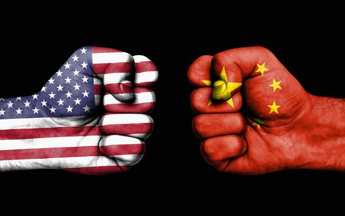 Two fists squaring off, with one decorated as the American flag, and the other as the Chinese flag.