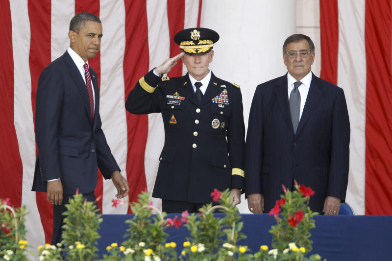 President Barack Obama arrives on stage at the Memorial Day Observance at the Memorial Amphitheater at Arlington National Cemetery, Monday, May 28, 2012. At center is Chairman of the Joint Chiefs of Staff Gen. Martin Dempsey and Defense Secretary Leon Panetta is at right. (AP Photo/Charles Dharapak)
