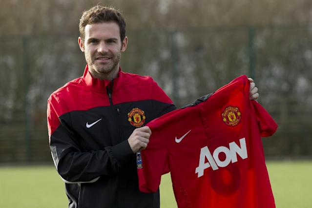 Manchester United's new signing Juan Mata displays his new shirt before a press conference at the team's Carrington training ground, Manchester, England, Monday, Jan. 27, 2014. With Manchester United in danger of missing out on the Champions League next season, Juan Mata's arrival at Old Trafford for a club record fee of 37.1 million pounds ($61.2 million) is certainly an emergency move. But it also marks the first step in the rebuilding process of England's most titled club. After a botched transfer campaign last summer that was followed by the club's lackluster first half of the season, United now looks determined to allow manager David Moyes the opportunity to build his own team.(AP Photo/Jon Super)