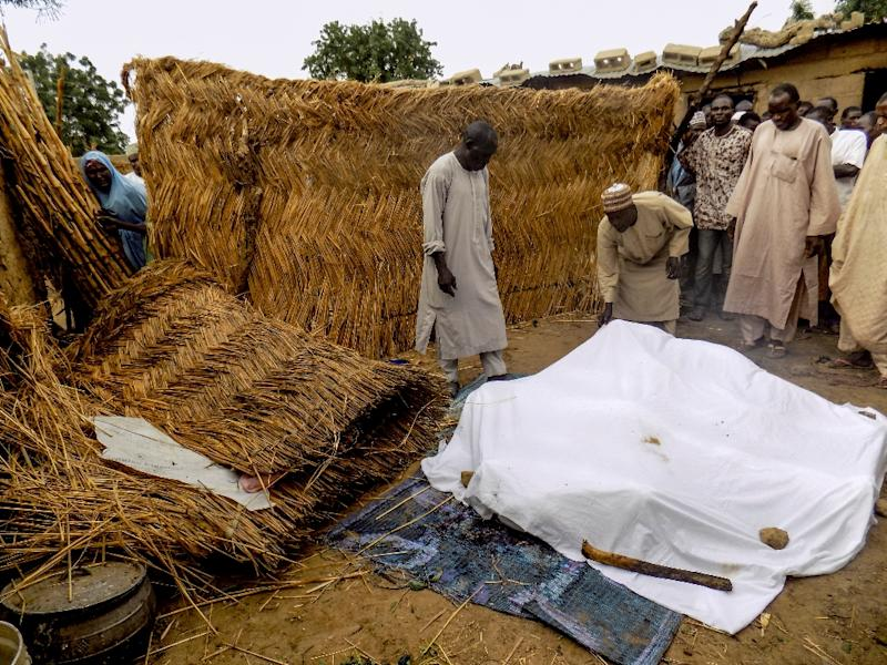 Residents cover victims of a Boko Haram suicide bombing attack in Koffa, northern Nigeria, on June 19, 2017