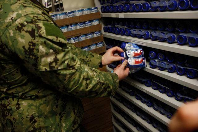 A guard displays cans of Ensure used to force feed detainees at Guantanamo.