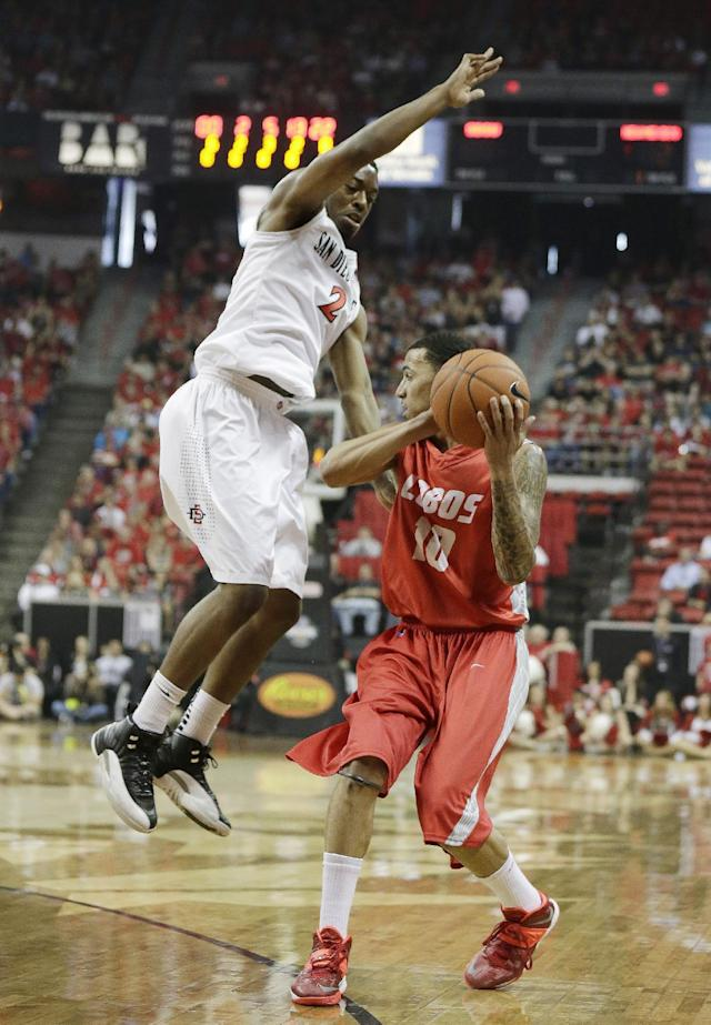 New Mexico's Kendall Williams, right, passes while covered by San Diego State's Xavier Thames during the first half of an NCAA college basketball game for the Mountain West Conference tournament championship on Saturday, March 15, 2014, in Las Vegas. (AP Photo/Isaac Brekken)