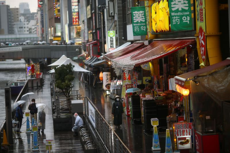FILE PHOTO: A woman, wearing protective mask following an outbreak of the coronavirus disease (COVID-19), walks on an almost empty street in the Dotonbori entertainment district of Osaka