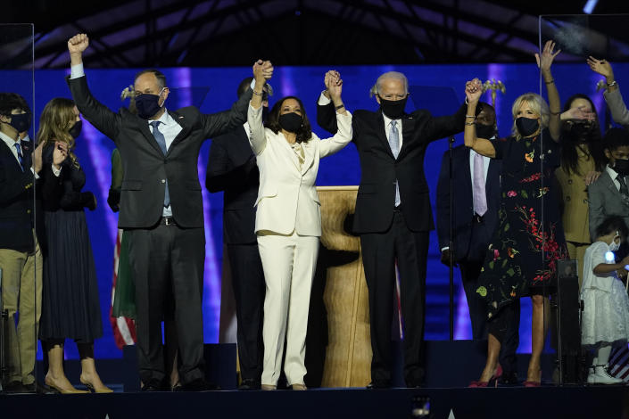 From left, Doug Emhoff, husband of Vice President-elect Kamala Harris, Harris, President-elect Joe Biden and his wife Jill Biden on stage together, Saturday, Nov. 7, 2020, in Wilmington, Del. (Andrew Harnik/Pool via AP)
