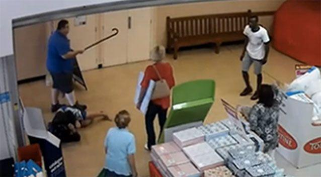 The man in the blue shirt fends off the attacker with his walking stick, forcing him out of the store. Picture: supplied