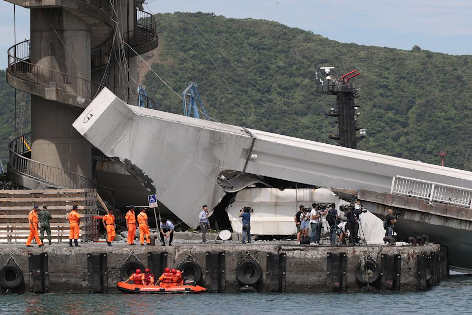 Rescue workers and media can be seen at the cement footing of the bridge hangs in the air.