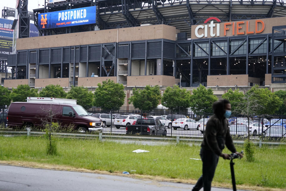 A man rides a scooter past CitiField after a baseball game between the Atlanta Braves and the New York Mets was postponed due to inclement weather Friday, May 28, 2021, in New York. (AP Photo/Frank Franklin II)