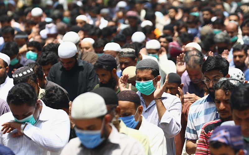Muslims wear face masks as they participate in Friday prayers on a road side in Karachi - Shutterstock