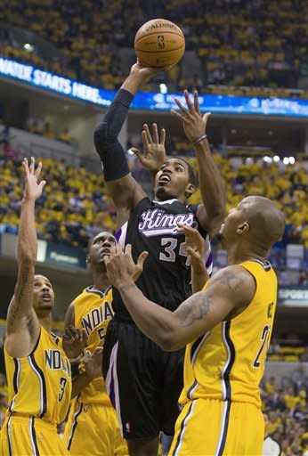 Sacramento Kings' Jason Thompson goes up between Indiana Pacers defenders, including George Hill, left, and David West, right, during the first half of an NBA basketball game in Indianapolis on Saturday, Nov. 3, 2012. (AP Photo/Doug McSchooler)