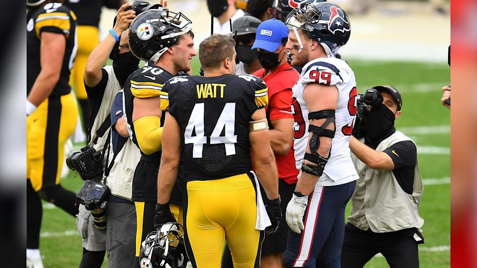 T.J., Derek, and J.J. Watt converse on the football field during a game between the Pittsburgh Steelers and the Houston Texans.