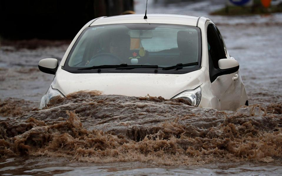 A car attempts to drive through floodwaters in Hathern, Leicestershire - Darren Staples / Alamy Live News