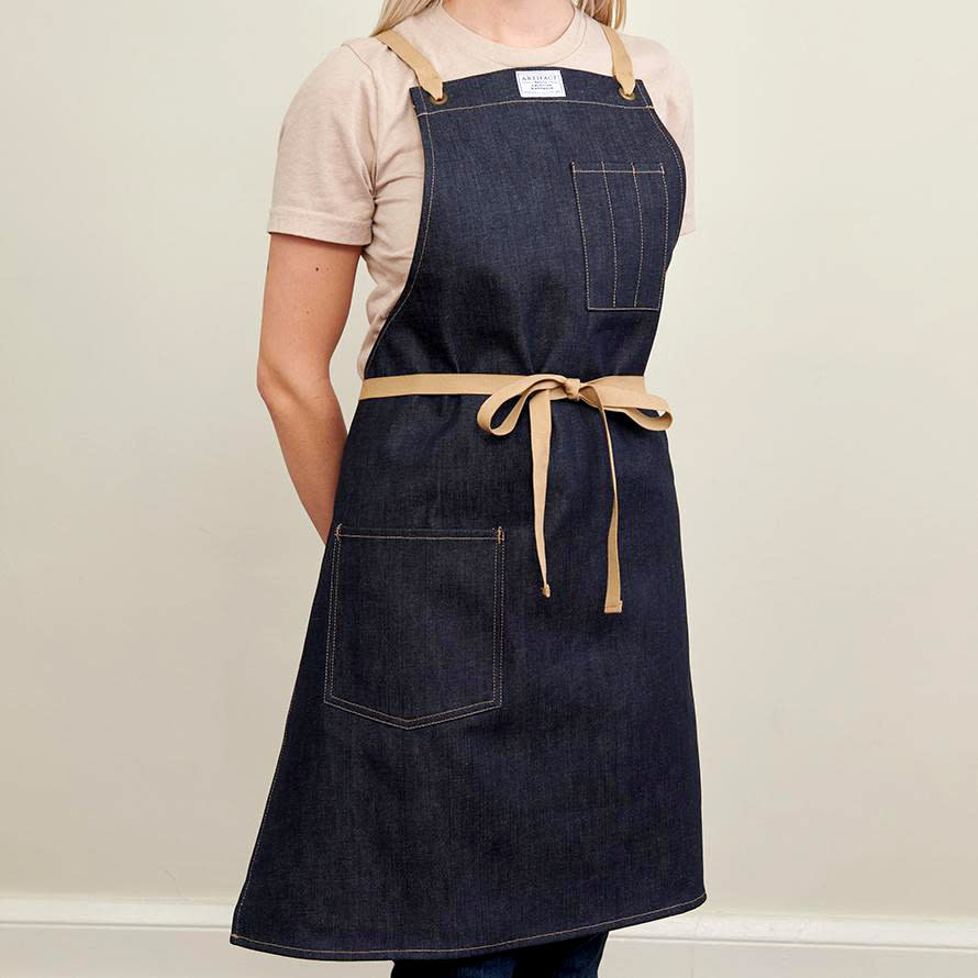 """<p>Durable but breathable, <a href=""""https://www.marthastewart.com/1538212/denim-crafts"""" rel=""""nofollow noopener"""" target=""""_blank"""" data-ylk=""""slk:denim has long been the material of choice"""" class=""""link rapid-noclick-resp"""">denim has long been the material of choice</a> for apron-wearing workers. """"We have a 1940s Sears Hercules denim apron we drew inspiration from,"""" Chris Hughes, the founder of <a href=""""https://artifactaprons.com/"""" rel=""""nofollow noopener"""" target=""""_blank"""" data-ylk=""""slk:Artifact Aprons"""" class=""""link rapid-noclick-resp"""">Artifact Aprons</a>, says of designing this style. """"Raw denim aprons look amazing over time and use, and we knew Japanese Kurabo denim would achieve the right look and feel.""""</p> <p><strong><em>Shop Now: </em></strong><em>Artifact Aprons No. 445T Kurabo Denim Apron with Cotton Cross-Back Ties, $80, </em><a href=""""https://artifactaprons.com/products/copy-of-cone-denim-culinary-apron-w-cross-back-ties"""" rel=""""nofollow noopener"""" target=""""_blank"""" data-ylk=""""slk:artifactaprons.com"""" class=""""link rapid-noclick-resp""""><em>artifactaprons.com</em></a><em>. </em></p>"""