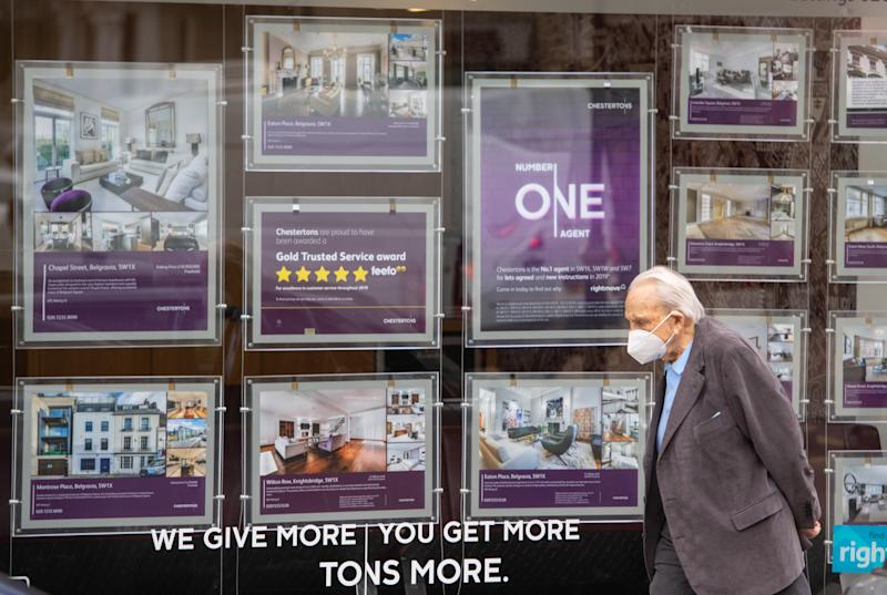 A man wearing a protective face mask passes an estate agents window in Knightsbridge, London, as annual house price growth ground to a halt in June, with property values down by 0.1% year on year, according to Nationwide building society. (Photo by Dominic Lipinski/PA Images via Getty Images)