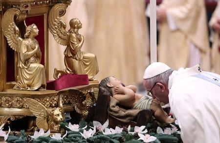 Pope Francis kisses the figure of Baby Jesus as he arrives to lead a mass to mark the World Day of Peace in Saint Peter's Basilica at the Vatican, January 1, 2019. REUTERS/Tony Gentile