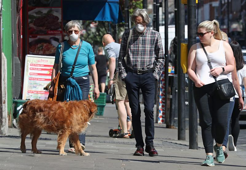 People wearing face masks walk past closed shops in Haringey, London, after the introduction of measures to bring the country out of lockdown.