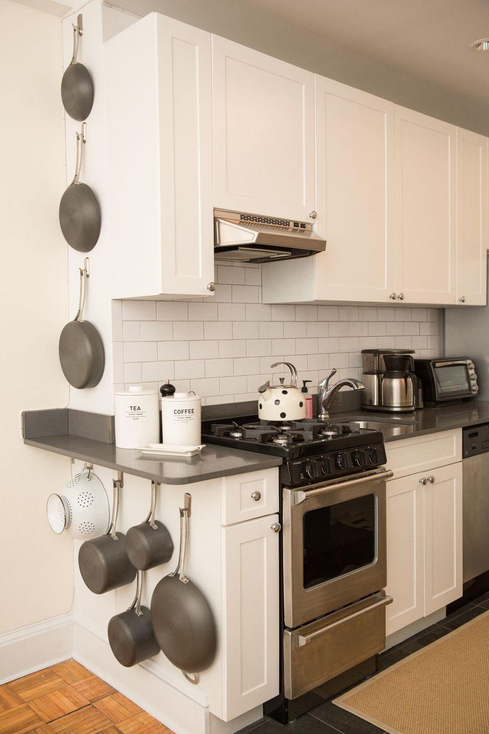 """<p>Instead of taking up valuable cabinet space with these clunky items, use Command Hooks to hang them on an unused wall, <a href=""""https://www.goodhousekeeping.com/home/organizing/a43607/professional-organizer-kitchen-makeover/"""" rel=""""nofollow noopener"""" target=""""_blank"""" data-ylk=""""slk:like this pro organizer did"""" class=""""link rapid-noclick-resp"""">like this pro organizer did</a>. S<span class=""""redactor-invisible-space"""">tart by hanging the biggest items first, then incorporate the medium-sized ones and finish with the smallest items. </span></p><p><span class=""""redactor-invisible-space""""><a class=""""link rapid-noclick-resp"""" href=""""https://www.amazon.com/Command-Utility-Medium-6-Hooks-17001-6ES/dp/B000FSORW4?tag=syn-yahoo-20&ascsubtag=%5Bartid%7C2164.g.35037072%5Bsrc%7Cyahoo-us"""" rel=""""nofollow noopener"""" target=""""_blank"""" data-ylk=""""slk:SHOP COMMAND HOOKS"""">SHOP COMMAND HOOKS</a><br></span></p>"""