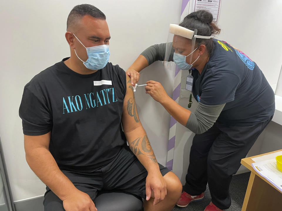 In this photo released by New Zealand Ministry of Health, Aaron Te Moananua, left, receives a dose of the Pfizer COVID-19 vaccine in Auckland, New Zealand, Tuesday, March 9, 2021. New Zealand has opened its first large vaccination clinic as it scales up efforts to protect people from the coronavirus. (New Zealand Ministry of Health via AP)