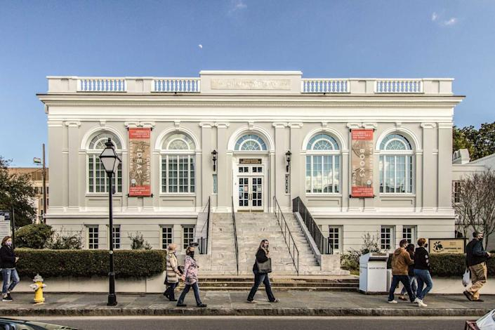 Exterior Of The Historical Charleston Library Society Building while pedestrians walk in front