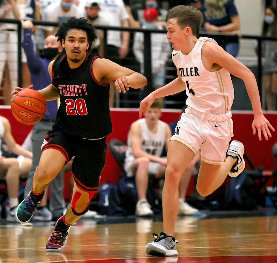 Trinity guard Malachi Farr (20) gets past Keller gaurd Grayson Price (4) during the second half of a 6A Bi-District High School Basketball playoff game played Monday, February 22, 2021 at Colleyville Heritage High School. (Steve Nurenberg Special to the Star-Telegram)