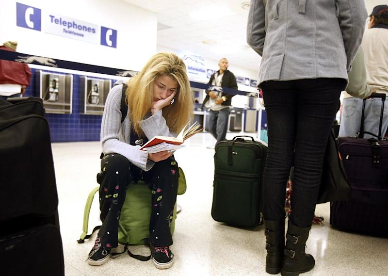 Jamie Collier, 18, remains engrossed in her book while waiting to board her bus at the Raleigh Greyhound Station in downtown Raleigh, N.C., on Tuesday, Nov. 26, 2013. A freshman at N.C. State University, she is traveling home to the Washington, D.C., area for a week to be with her family for the Thanksgiving holiday. (AP Photo/The News & Observer, Corey Lowenstein)