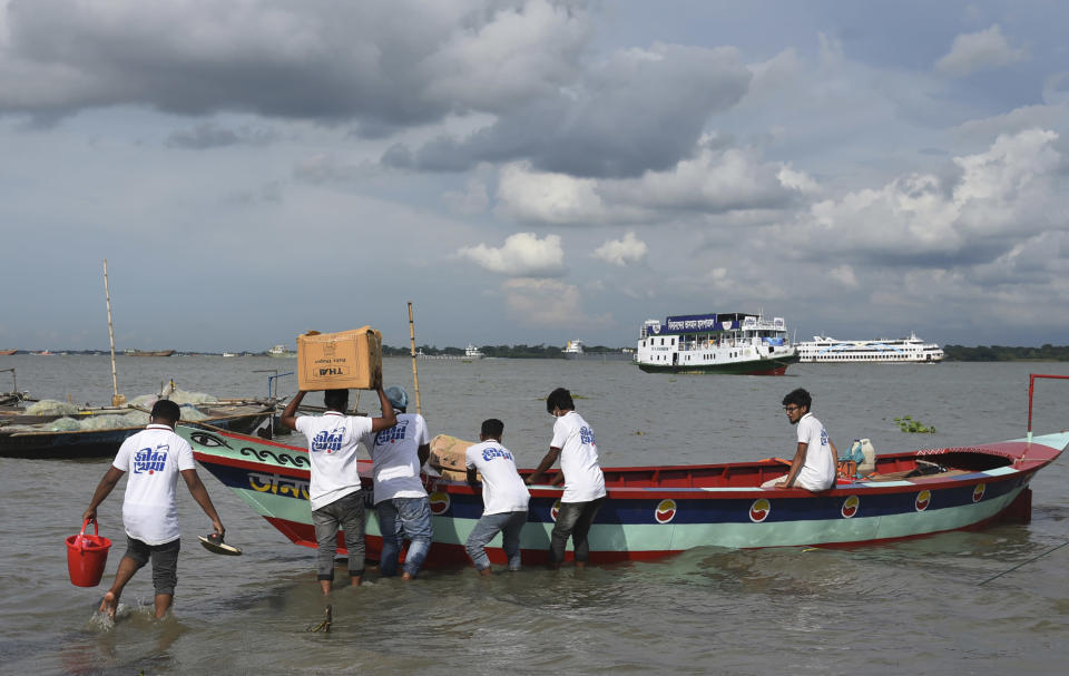 In this photo provided by Bidyanondo Foundation, volunteers load medical supplies to be carried on boat hospital, in Chandpur District in eastern Bangladesh, on Sept. 12, 2020. A Bangladeshi charity has set up a floating hospital turning a small tourist boat into a healthcare facility to provide services to thousands of people affected by this year's devastating floods that marooned millions. (Bidyanondo Foundation via AP)