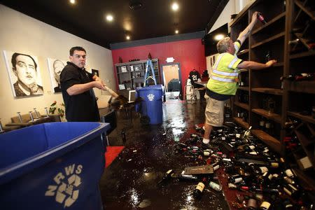Rick Ruiz (L) and Tyler Paradise gather broken wine bottles from the floor of their Cult Following Wine Bar after an earthquake in Napa, California August 24, 2014. REUTERS/Stephen Lam
