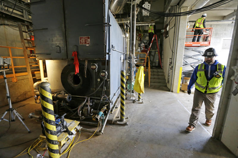 In this March 16, 2017 photo, Bryan Troupe, right, a safety officer at the West Point Treatment Plant in Seattle, walks through an area where workers were repairing a boiler and stringing temporary power sources after the room was flooded nearly to the ceiling during a massive equipment failure. The county-run facility has been hobbling along at about half-capacity since the Feb. 9 electrical failure resulted in catastrophic flooding that damaged an underground network of pumps, motors, electric panels and other gear. (AP Photo/Ted S. Warren)