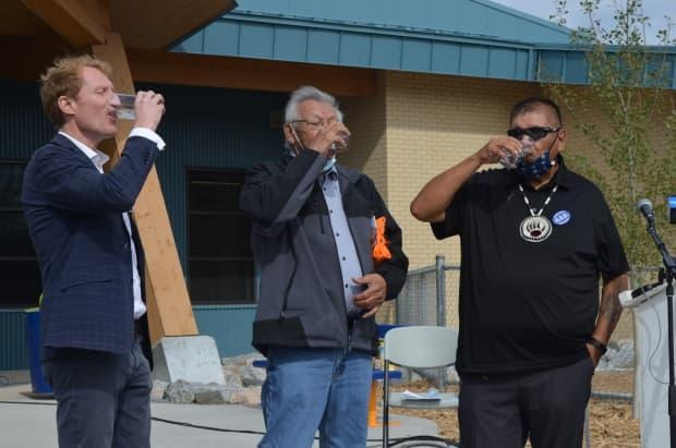 From left: Federal Indigenous Services Minister Marc Miller, Herb Redsky, an elder from Shoal Lake 40 First Nation, and Vernon Redsky, chief of Shoal Lake 40 First Nation, enjoy a glass of tap water to celebrate the lifting of water advisories for the community.  (Sarah Petz/CBC - image credit)