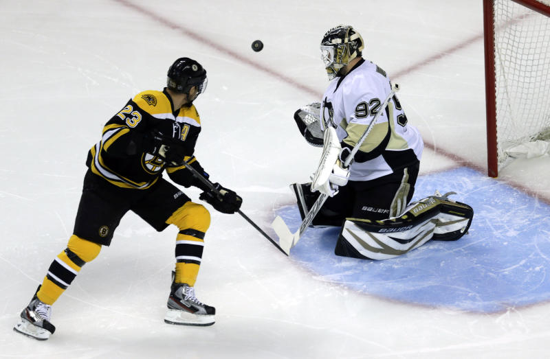 Pittsburgh Penguins goalie Tomas Vokoun (92) deflects the puck in front of Boston Bruins center Chris Kelly (23) during the first period of Game 4 in the Eastern Conference finals of the NHL hockey Stanley Cup playoffs, in Boston on Friday, June 7, 2013. (AP Photo/Charles Krupa)