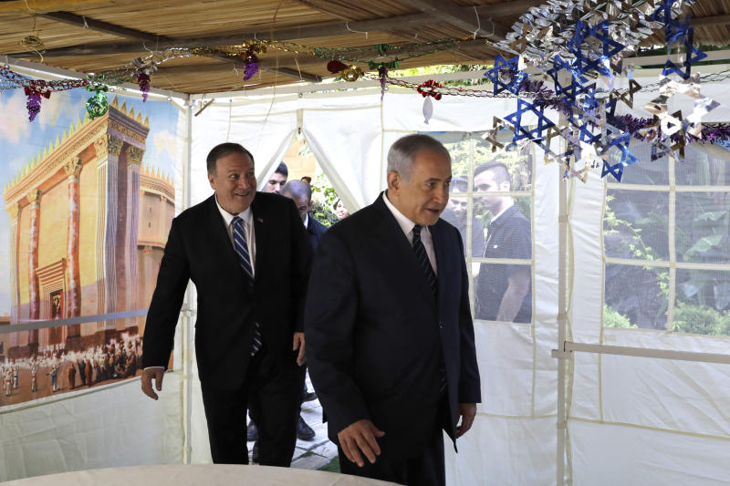 U. S. Secretary of State Mike Pompeo, left, and Israeli Prime Minister Benjamin Netanyahu, enter a sukkah, a traditional shack built for the weeklong Jewish holiday of Sukkot, at the Prime Minister's residence in Jerusalem. Friday, Oct. 18, 2019. (AP Photo/Sebastian Scheiner, Pool)