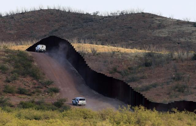 FILE - This Oct. 2, 2012 file photo shows U.S. Border Patrol agents patrolling the border fence near Naco, Ariz. The United States has spent billions of dollars over the last decade fencing a third of its southwest border with Mexico in an attempt to stop the flood of illegal immigrants. (AP Photo/Ross D. Franklin, File)