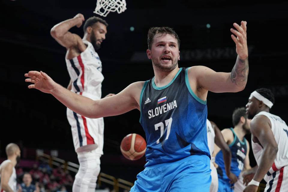 Slovenia's Luka Doncic (77) reacts after scoring against France's Rudy Gobert, left, during a men's basketball quarterfinal round game at the 2020 Summer Olympics, Thursday, Aug. 5, 2021, in Saitama, Japan. (AP Photo/Eric Gay)