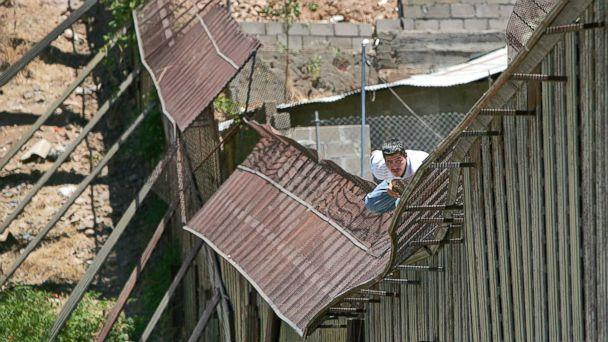 PHOTO: In this May 31, 2006, file photo, a man climbs over the international border into Nogales, Ariz., from Nogales, Mexico. (AP)