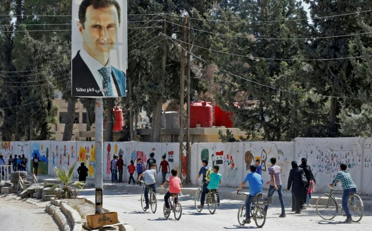 A portrait of Syria's President Bashar al-Assad overlooks students heading back to school in the former rebel-held enclave of Eastern Ghouta