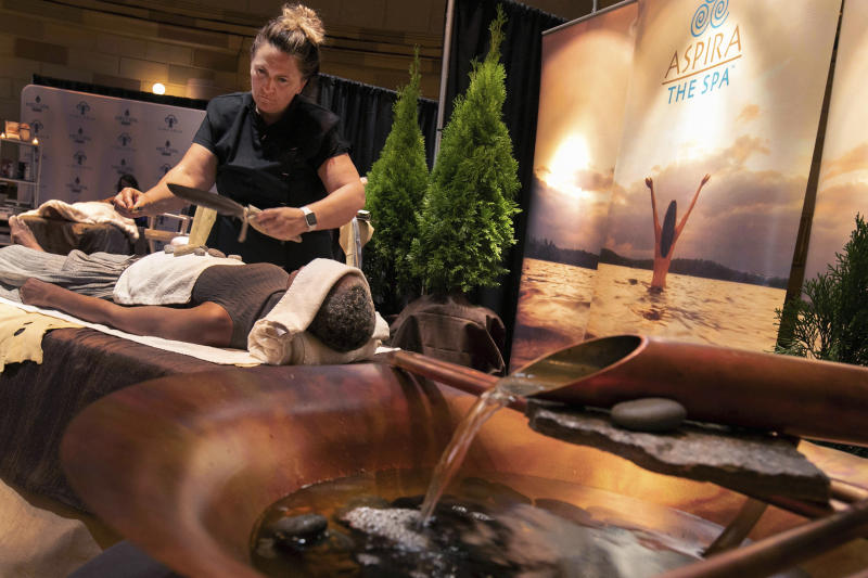 In this Tuesday, Aug. 6, 2019, photo, lead therapist Mickaela Sommers, at Aspira Spa at the Ostoff Resort, in Elkhart Lake, Wisc., demonstrates DOHI, a tribal purifying and cleansing ritual, during the 2019 International Spa Association event, in New York. (AP Photo/Richard Drew)