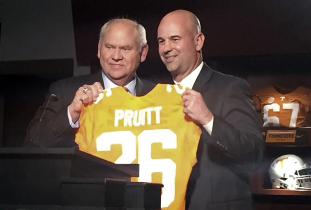 New Tennessee football coach Jeremy Pruitt, right, receives a personalized jersey from athletic director Phillip Fulmer during his introductory news conference Thursday, Dec. 7, 2017, in Knoxville, Tenn. (AP Photo/Steve Megargee)