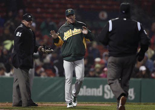 Oakland Athletics manager Bob Melvin disputes a call with home plate umpire Hunter Wendelstedt (21) and Jerry Layne during the fourth inning of a baseball game against the Boston Red Sox at Fenway Park in Boston Tuesday, April 23, 2013. (AP Photo/Winslow Townson)