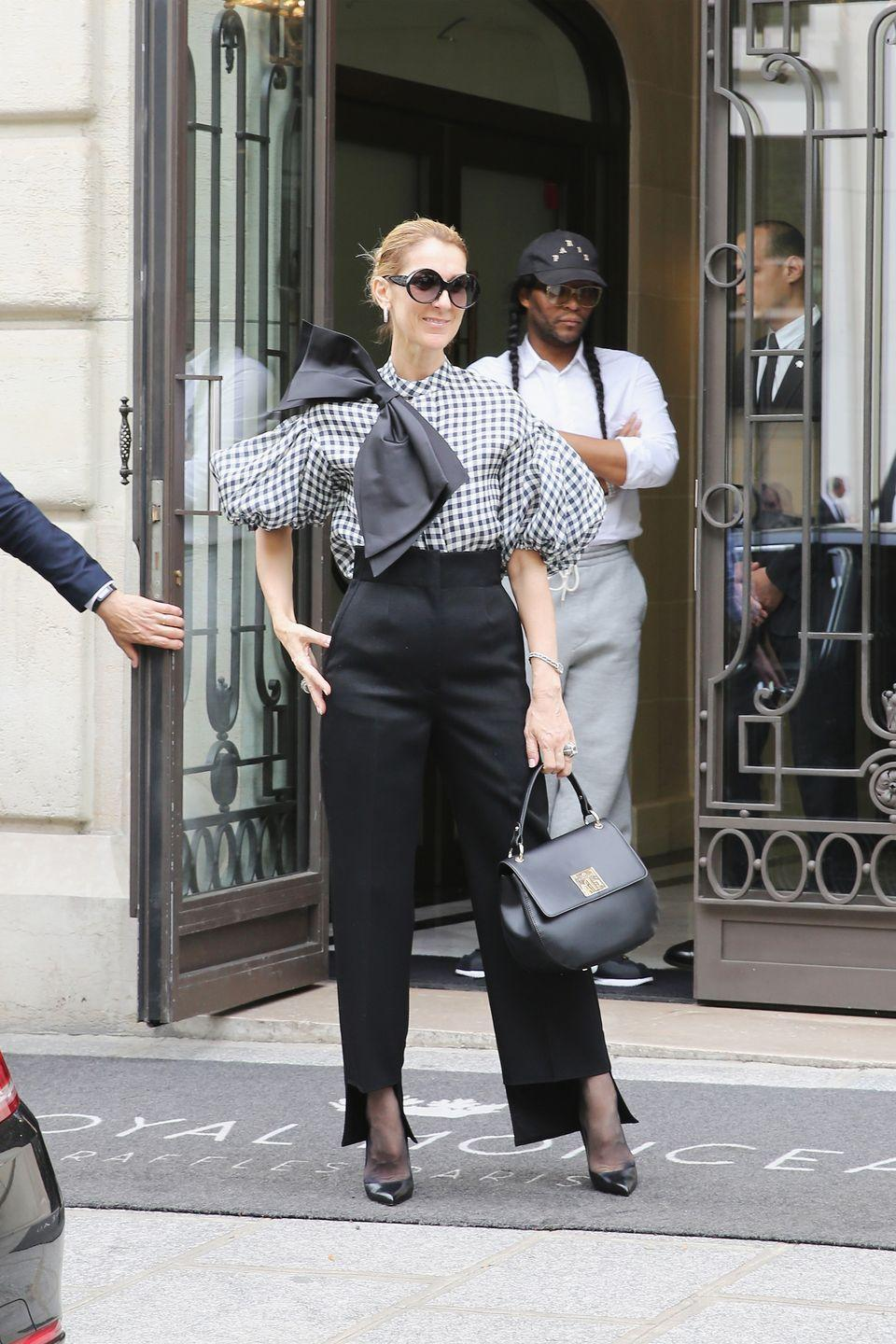 <p>In high-waisted Celine trousers, a Dice Kayek blouse detailed with a giant bow, Tom Ford heels, and a bag from her own collection while out in Paris. </p>